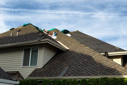 Home with roof being replaced showing new shingles, felt paper, and tools