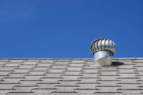 An exterior exhaust vent on top of a roof.